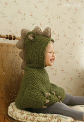 crochet pattern for dragon poncho. The hooded poncho has cute pockets with nails, decorated with spikes and small ears. Worked bottom up with aran weight yarn. Perfect for a little boy or girl to look cute!