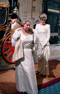 The queen, dressed in her best formal attire arrives with Princess Diana in a carriage to open Parliament in 1991.