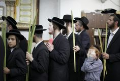 Ultra-Orthodox Jewish men queue as they wait for a Rabbi to check their palm fronds for blemishes at a Jewish seminary in Jerusalem's Mea Shearim neighborhood. The branches are used to cover the roof of the ritual booths known as sukkah, used during the week-long Jewish holiday of Sukkot, which begins at sundown on Sunday.