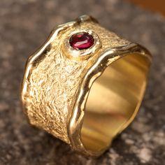 Geel gouden ring 14 karaat Met 4mm. granaat (cabochon geslepen) gezet in een ruw gefreesden zetting . Achtergrond ruw gefreest . Ringmaat:15,5 mm. Breedte max: 12 mm.