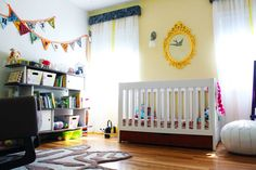 Cheerful little nursery with white curtains and a painted yellow mirror from Ikea above the crib.