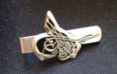 Silberner Krawattenhalter in Jugendstil. 800 gestempelt. Das Motiv des Krawattenhalters ist in den Vertiefungen schwarz unterlegt. Niellotechnik. Gebrauchter, aber tragbarer Zustand. Wirkt sehr...