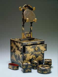 Kyodai (makeup set), 19th century, Wood, lacquer, bronze, brass, Japan, H: 25 5/8 in, L: 10 3/4 in (H: 65.1 cm, L: 27.3 cm). This is a Kyodai, or makeup set. It is ornamented with chrysanthemum-shaped gilt metal fittings and gold maki-e shells and aquatic plants. The set includes a water container, oil container, two white power boxes, and a mirror.