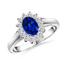 At the core of a scintillating floral halo is an oval blue sapphire, held in a prong setting. This oval blue sapphire ring is inspired by Princess Diana's beautiful engagement ring. #engagementring