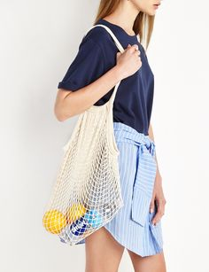A neutral French net market bag, like this one from Pixie Market, can be a beach bag or everyday accessory.