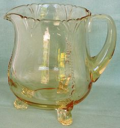 This is the lovely Heisey empress elegant glass in sahara yellow. The jug or pitcher is approx 6 3/4 inches tall. It holds about 48 ounces to the brim. It has 3 dainty dolphin shaped feet
