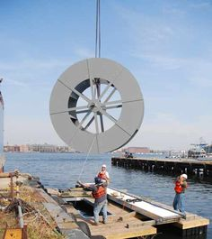 The specially designed 12 ft diameter river wheel developed by the Waterwheel Factory for this project is lowed into place on the barge unit.