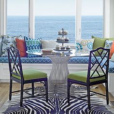 The breakfast room takes the palette a step further, incorporating playfully patterned fabrics in shades of turquoise, green, and orange.