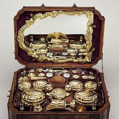 Another view of Toilet set in original leather case, ca. 1743–45, German, Augsburg. 14 identified German (Augsburg) goldsmiths and other German artisans; Japanese (Imari) porcelain maker   Medium: Gilt silver, hard-paste porcelain, cut glass, walnut, carved and partially gilt coniferous wood, blind-tooled and partially gilt leather, partially gilt steel and iron, textiles, moiré paper, hog's bristle. This Set embodies the ultimate expression of princely splendor in precious metalwork.