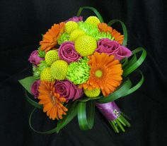 Bright mix of orange gerbera daisies, yellow craspedia, hot pink roses and green mums with looped grasses.