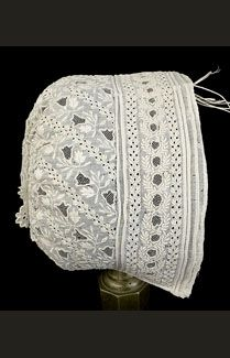 Whitework baby bonnet, circa 1850. Made from sheer cotton batiste covered with very fine hand-embroidered whitework. The intricate pattern features a variety of leaves rendered in padded satin stitch with eyelet berries and open work bell-shaped flowers.