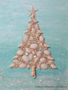 I created this gorgeous coastal Christmas tree using pretty white shells and crushed shells. At the top I added a real starfish which, along with the white shells, has been finished with a pearlized paint. I handpainted the backround with pretty coastal colors and added snow and