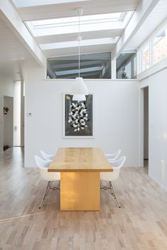 The area that was formerly the atrium now houses the dining room. The table is Room & Board, and the pendants IKEA. The poster is another Herman Miller trade poster found at a Berkeley shop.