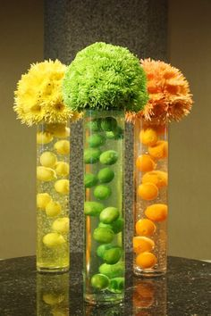 """Citrus Surprise"" Cool icy and refreshing. A gelatin like material suspends fresh citrus fruits in tall glass cylinders. Spheres of spider mums top these citrus coolers."