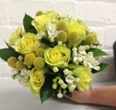 Yellow and white wedding flower theme in a hand-tied bridal bouquet with yellow roses, craspedia and white bouvardia. | Wedding Flowers Liverpool, Merseyside, Specialist Bridal Florist, Booker Flowers and Gifts, Booker Weddings Liverpool