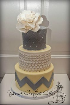Love the clean chevron design on the bottom layer, with the more elegant design on the top layer, and the fabulous huge flower on top! #wedding cake, special occassion cake, chevron wedding theme, flower on cake, yellow, ivory, grey