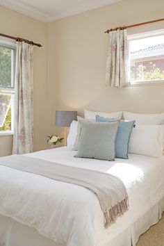 Soft tones, sky blue, pale green and light grey cushions, white bedding, grey lamp shades, guest bedroom