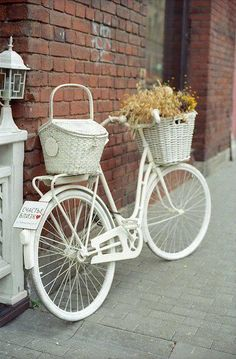 All white bicycle with white baskets on the front and the back, sitting against a brick wall.