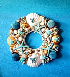 16 SEA SHELL WREATH EMBELLISHED WITH WHITE SCALLOPS, LARGE CUP SHELLS, FLAT PECTANS, AND A VARIETY OF EXOTIC SEA SHELLS. IN ADDITION,THE WREATH IS DECORATED WITH SEASIDE BLUE STAR FISH, SEA URCHINS,AND NATURAL BLUE LIMPETS.  SOLID WOOD BACKING WITH HOOK FOR EASY HANGING.  INNER DIAMETER-5  PERFECT ADDITION TO YOUR ENTRY DOOR AND GREAT WALL DECOR.  DESIGN# 40024  PLEASE SEE SPECIAL INSTRUCTIONS BELOW FOR OUTDOOR CARE.  EXCLUSIVELY FROM ELLIES COLLECTIONS, ETC. OCEANSIDE, CA. MADE IN USA  SAFE…