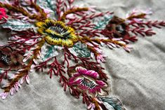 like the intricate feathery stitches and the details - applique, ribbon. the colors.
