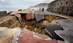 Members of a television crew stand near a hole in the Paseo Nuevo in San Sebastian - Provided by Reuters