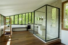 A spacious glass shower shaped like a cube and two wash basins are on the far end of the lofty master bedroom
