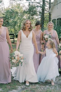 This beautiful bride is walking confidently with her flower girl holding her hand and her beautiful bride tribe walking behind her! Your wedding day is all about having the right people by your side. So its important for them to look and feel their best as well! These bridesmaids are wearing the Pearl dress in Desert Rose from Kennedy Blue. With over a hundred styles, 44 colors, and sizes 00 - 32, your bridal party is sure to find the perfect bridesmaid dress!   bridesmaid dress planning