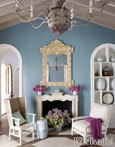 Pale blue room, with white trim, pink details, and an antique mirror