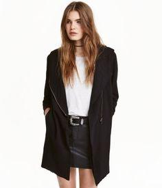 Schwarz. Jacke aus Sweatstoff mit gefütterter Kapuze, diagonalem Frontreißverschluss und Seitentaschen. Bündchen…