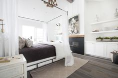 This crisp, white bedroom provides a modern take on cottage style. The space features wide-plank wood floors, a soaring white beadboard ceiling, and built-in shelving around a modern fireplace. Adjacent to the bedroom is a luxurious white marble bathroom with a frameless glass shower.
