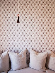 Wallpaper tricks the eye into seeing / feeling a lush button tufted fabric headboard/ wall panel