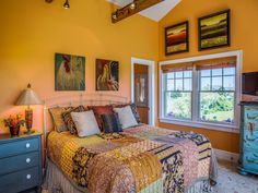A Whimsical Oceanside Cottage With Colorful Interiors...Bold Colorful Bedroom...Love The Chicken Paintings Over The Bed