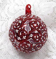 Margot Clark creates a red blown glass glass ornament with White 3D texture painted MUD design of scrolls and leaves. Each ornament created is a one-of-a-kind. The texture medium and paint brush used to paint the ornaments were both created to my specifications. Gift boxed. Ornament