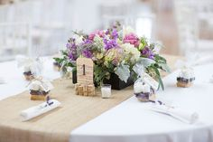 Low centerpiece with purple & green flowers | Lavender Infused Romantic Olde Dobbin Station Texas Wedding | Photograph by The Freckled Key  http://storyboardwedding.com/lavender-romantic-olde-dobbin-station-texas-wedding/