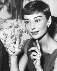 Adorable Audrey Hepburn looking like she's giving air quotes.