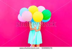 Woman is hides her head an air colorful balloons having fun over pink background