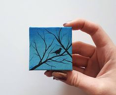 """TITLE // """"Little Bird"""" SIZE // 2 inch x 2 inch, 1 cm thick MEDIUM // Professional grade acrylics on stretched canvas. It is finished with a matt varnish. This is a tiny painting I created. It features a silhouette of a little bird sitting on a branch on a blue background. It is signed"""