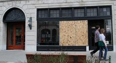 Boards cover broken windows Monday, March 7, 2016, at the Eldridge Hotel, 701 Massachusetts St., and Hobbs Inc., 700 Massachusetts St., not shown. One man was arrested early Monday morning on suspicion of throwing bricks through the windows.