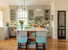 mid sized kitchen island with book shelves and a couple of striking blue chairs L shape kitchen in white with colorful tiles backsplash white countertop and stainless steel appliances of Tens of Inspiring Kitchen Islands with Storage and Chairs
