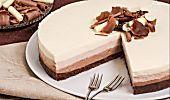 La cheesecake zebrata è una versione del dolce americano senza formaggio ma con latte condensato, yogurt e panna montata, variegato ai mirtilli.