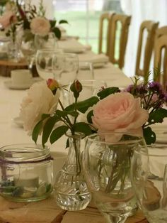 Small vases and jars filled with Homegrown roses