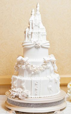 This week's Wedding Cake Wednesday is a three-tier stunner complete with a white chocolate castle topper and a layer of bling at the bottom! #wedding #cake