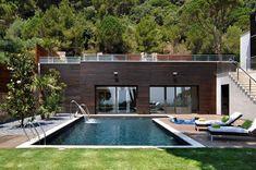 une grande piscine avec plage en bois composite et chaises longues dans le jardin