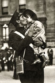 A soldier of the Canadian Expeditionary Force kisses his daughter goodbye before shipping off. Gaspé Harbour, Quebec, 1914.