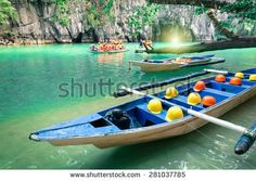 Longtail boats at cave entrance of Puerto Princesa subterranean underground river - Nature trip in Palawan exclusive Philippines destination - People with light equipment during adventurous excursion - stock photo