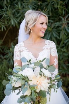 Romantic bridal up-do, teased wedding hairdo, unique long lace sleeves, romantic bridal beauty look, drop earrings // France Photographers