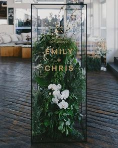 Make a big first impression on your guests with a glass-box installation filled with orchids and fresh ferns (the gold type really pops against the lush greenery!).