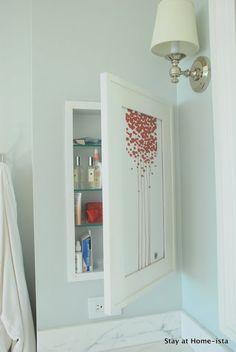 hidden medicine cabinet behind a piece of artwork