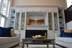 Custom Built living room space with gorgeous fire place and incredibly tall windows!