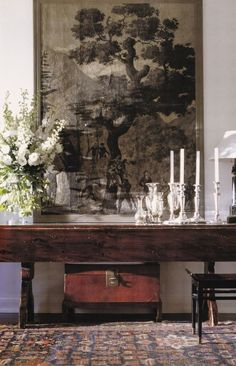 large-scale art, dark wood antiques, antique rug, ivory candles, vintage silver, white flowers